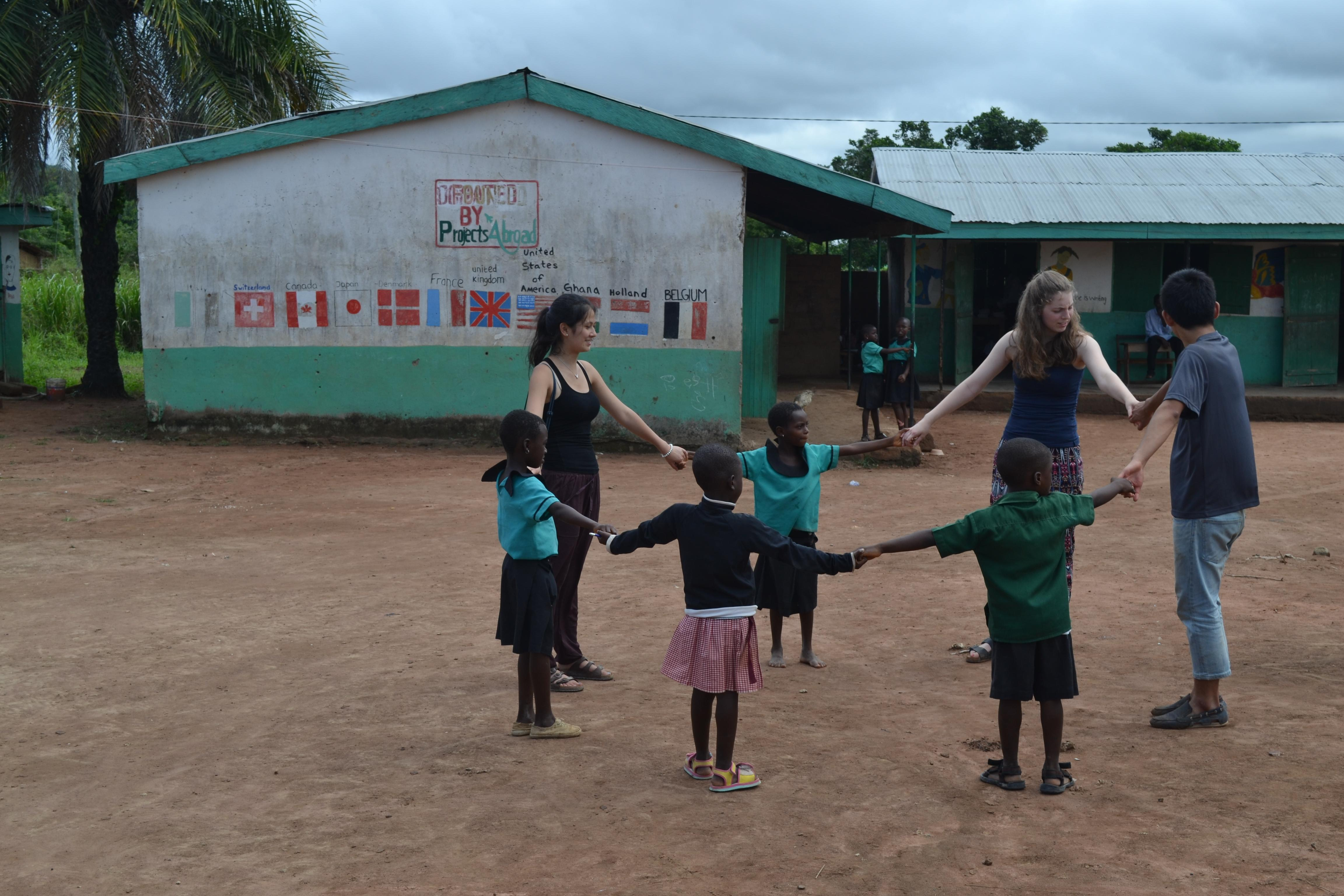 Local children do a fun activity outdoors with Projects Abroad volunteers working with children in Ghana as a team.